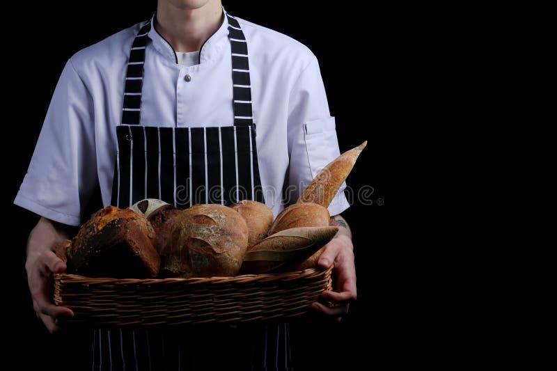 Baker houdt mand brood op zwarte ge?soleerde achtergrond royalty-vrije stock afbeeldingen