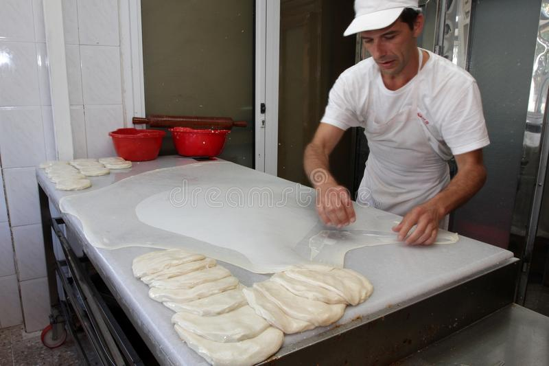 A baker knead dough for cheese pie with roller and flour in bakery in the city of Sofia, Bulgaria – sep 4 , 2015. Chef prepares stock image