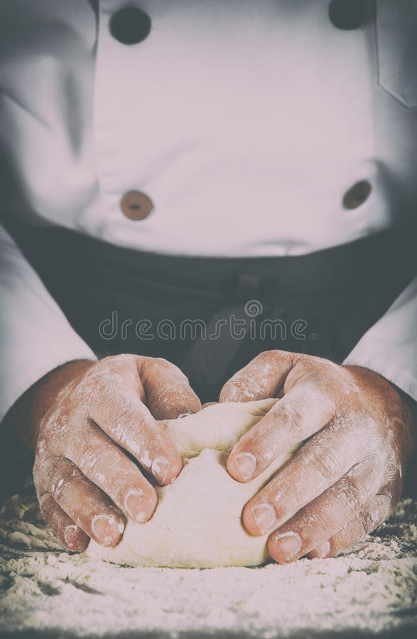 Baker kneading dough with his hands royalty free stock photography
