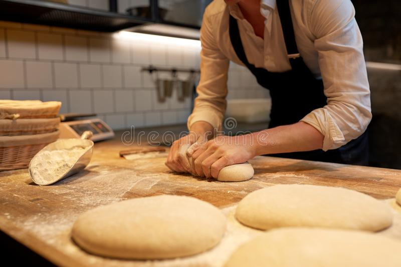 Baker making bread dough at bakery kitchen stock photo