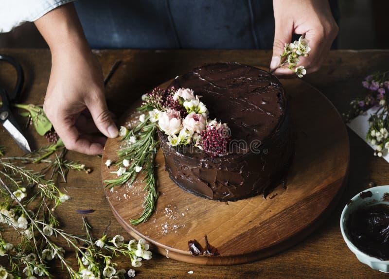 Baker Man Decorating Chocolate Cake met Bloemen stock foto