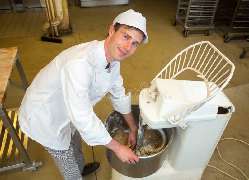 Baker met deeg het kneden machine in bakkerij royalty-vrije stock foto's