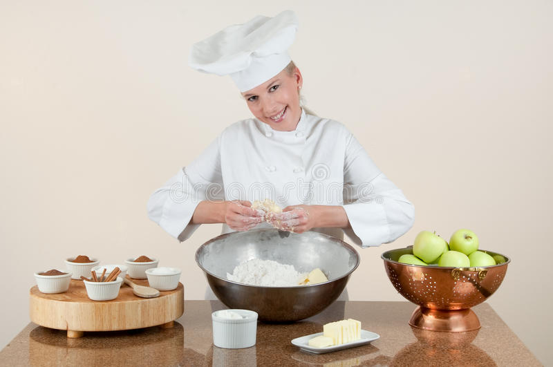 Baker Pinching Pie Dough. Assertive smiling attractive female Chef pinching butter and flour in making apple pie dough for crust at her bakery station against a royalty free stock photo