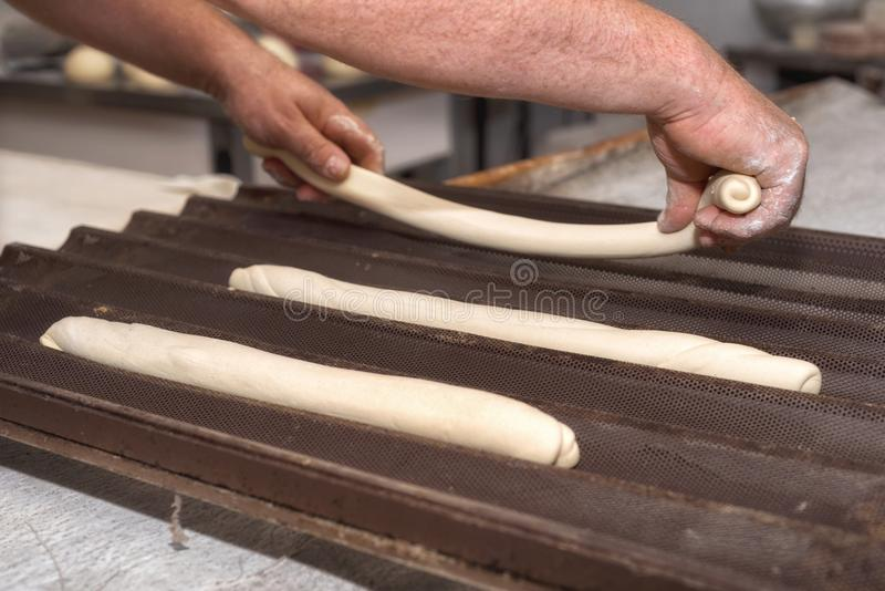 Baker preparing uncooked bread dough loaves ready to bake.  royalty free stock photo