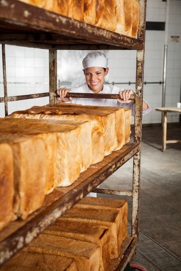 Baker Pushing Rack Full van vers Gebakken Broden in Bakkerij stock foto's