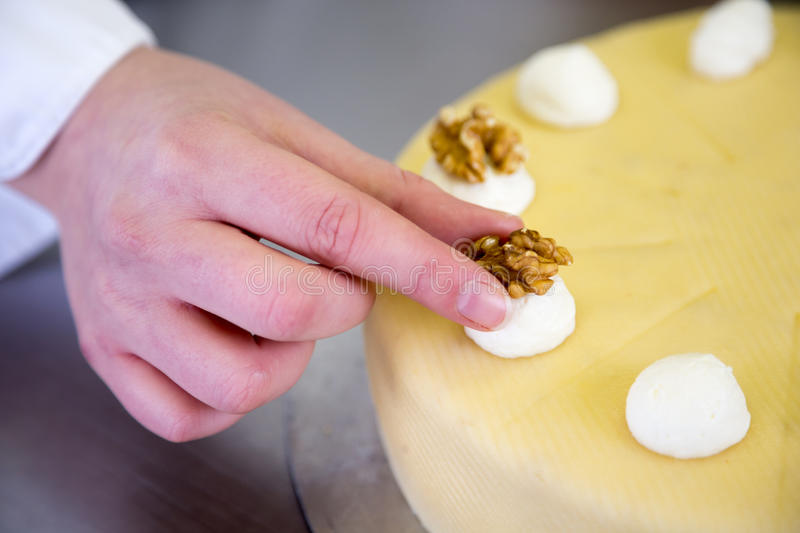 Baker puts walnut on cake in bakery royalty free stock images