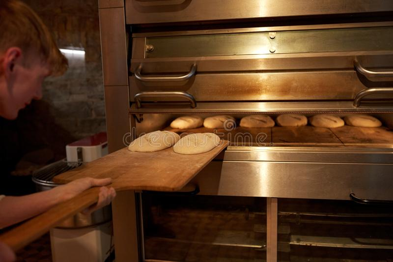 Baker putting dough into bread oven at bakery stock image