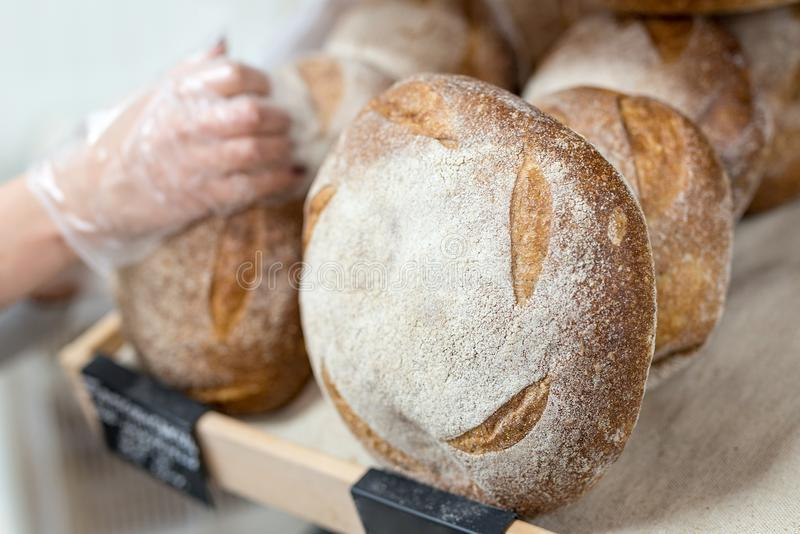 Baker& x27;s hand putting Loafs of warm tasty freshly baked bread in a bakery shop or market stock photo