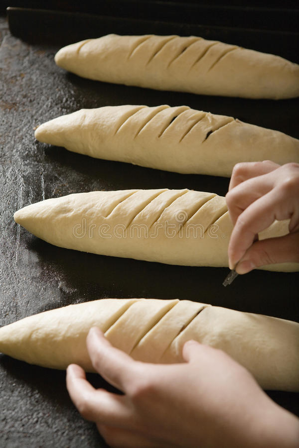 Baker Scoring Loaves Of Bread Dough royalty free stock photo