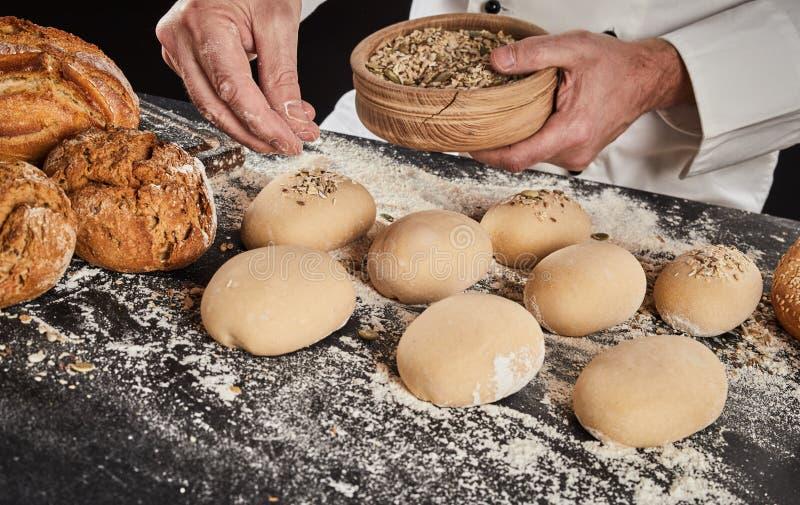 Baker sprinkling crushed grain and seeds on bun stock photos