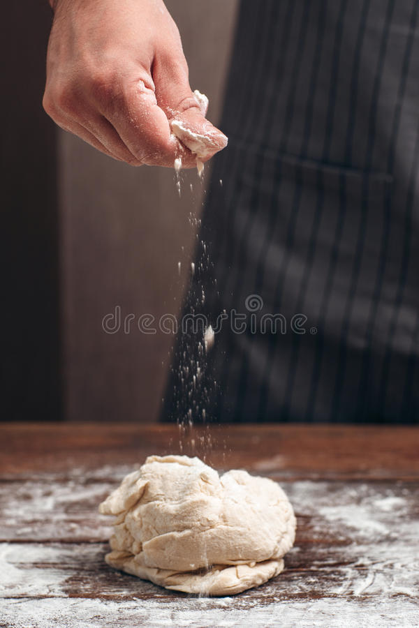 Baker sprinkling flour above raw dough royalty free stock image