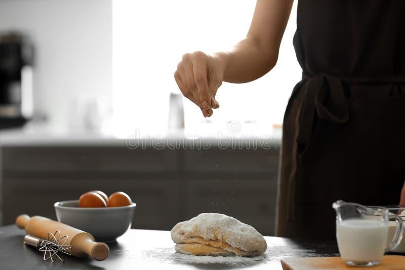Baker sprinkling flour on dough at table royalty free stock photos