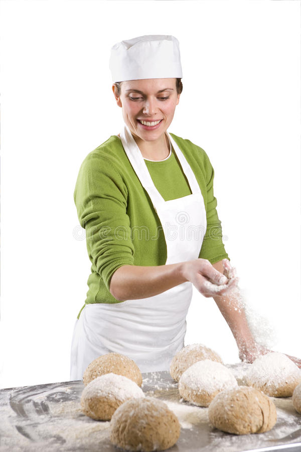 Baker sprinkling loaves of bread with flour royalty free stock image