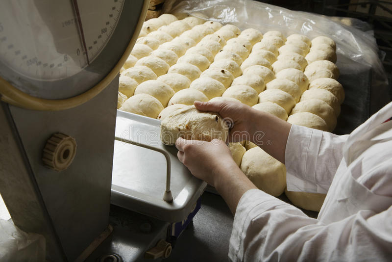 Baker Weighing Ball Of Bread Dough. Male baker weighing ball of bread dough in bakery royalty free stock image