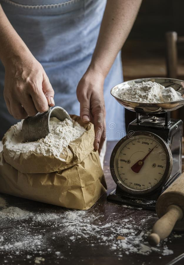Baker weighing flour on a scale stock image