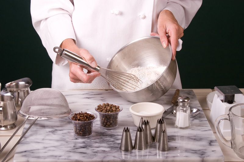 Baker whisking flour. Tight shot of a Baker whisking dry ingredients in a stainless steel mixing bowl for making pie dough royalty free stock image