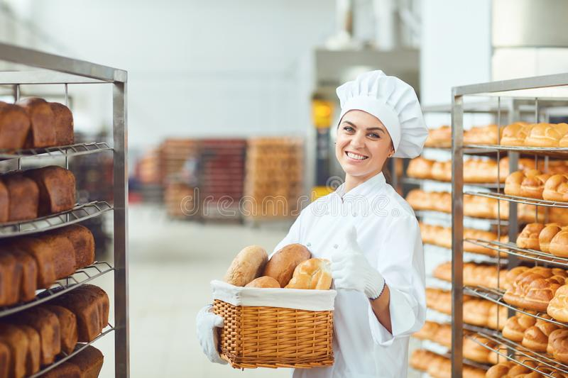 A baker woman holding a basket of baked in her hands at the bakery royalty free stock image