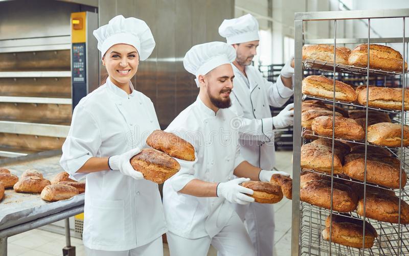 A baker woman holds fresh bread in a bakery. stock image