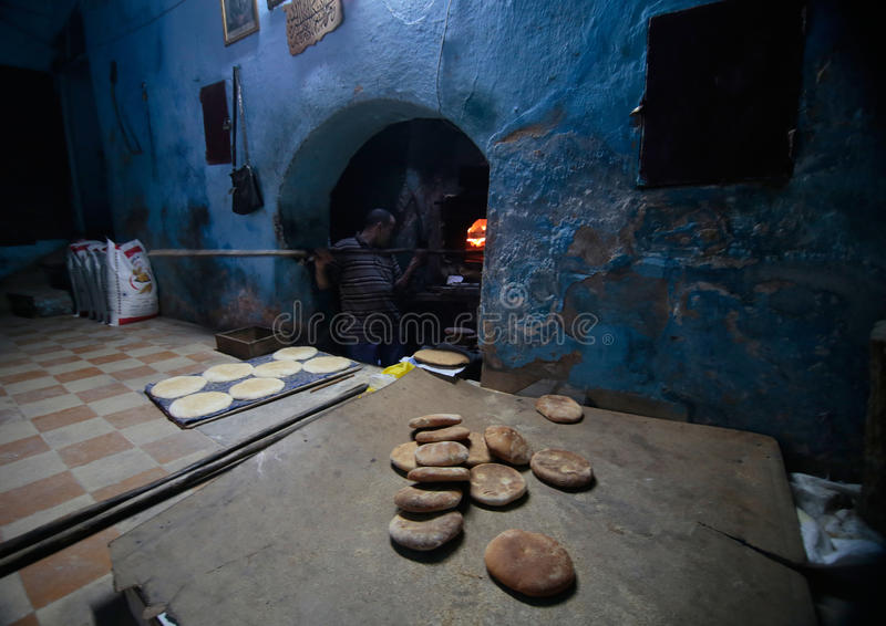 A baker at work in ancient Medina of Fez in Morocco. A baker slides the bread into an antique wood oven in a local bakery in the city of Fez in Morocco. Besides stock photo