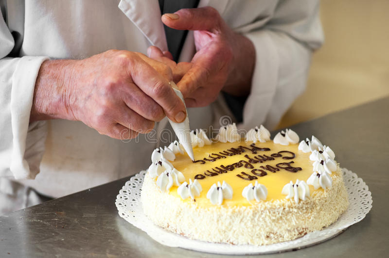Baker Writing Birthday Message on Top of Cake royalty free stock photos
