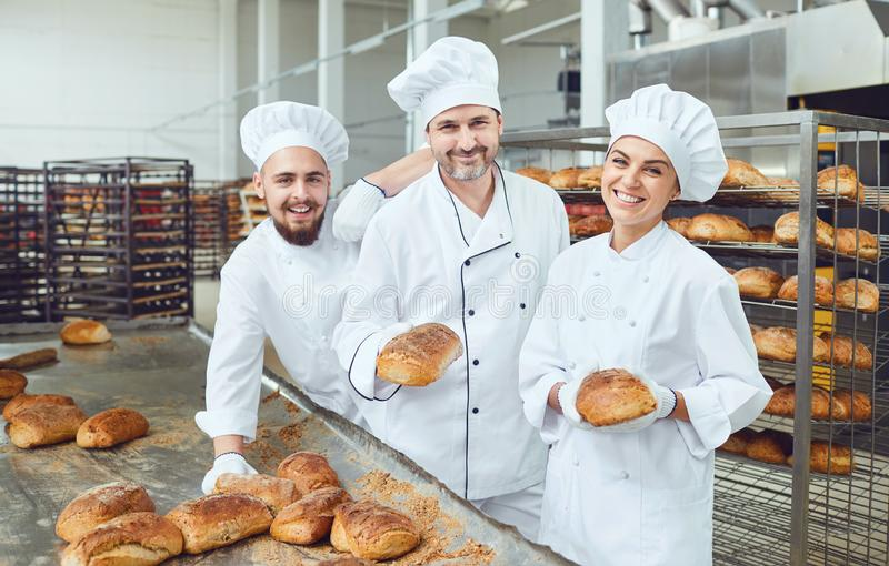 Bakers smiling holding fresh bread in their hands in a bakery royalty free stock images