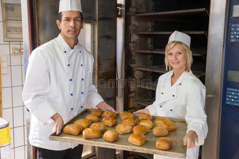 Bakers with tablet of bread in bakery or bakehouse royalty free stock photo