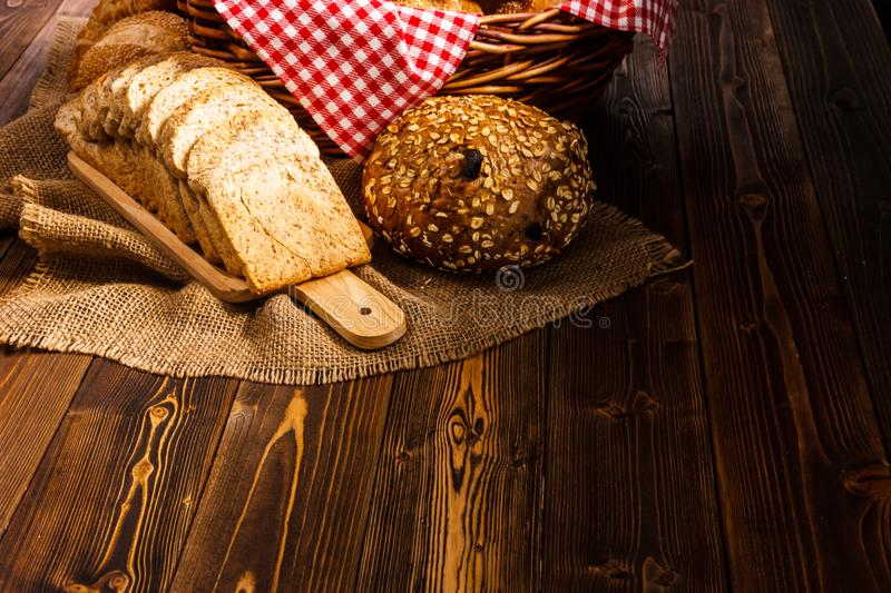 Bakery Assortment on wooden table on dark background. Still Life of variety of bread with natural morning light royalty free stock photography