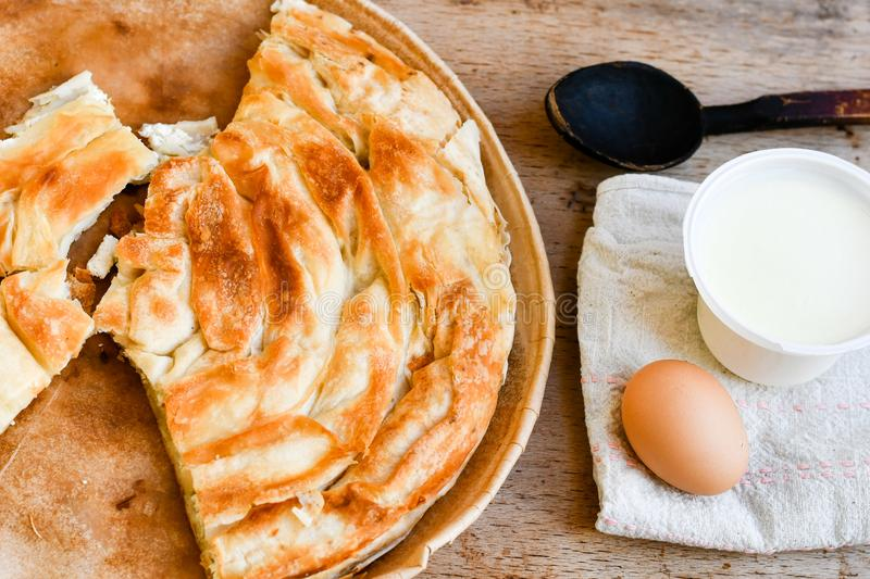 Bakery background – cheese pie. Bakery background – home made cheese pie, bio egg, yogurt and wooden spoon on wooden board royalty free stock photos