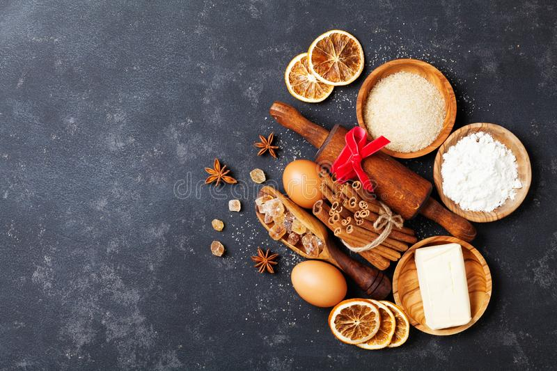 Bakery background with baking ingredients for christmas cooking top view. Flour, brown sugar, eggs and spices top view. stock photo
