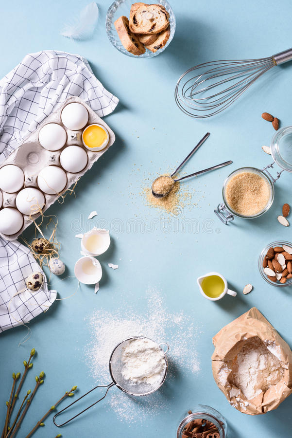 Bakery background, baking ingredients over blue kitchen countertop. Flour, egg, sugar and almond nuts. Top view. Bakery background, baking ingredients over blue stock photo