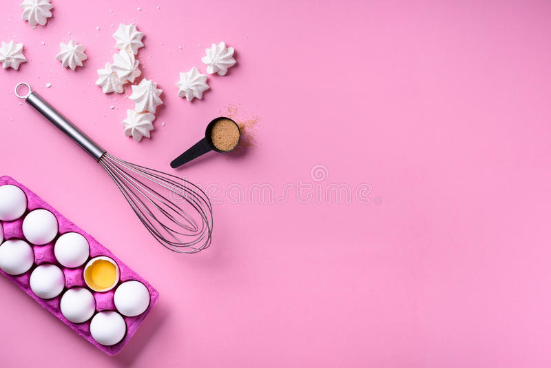 Bakery background frame. Cooking merengues, ingredients - eggs with sugar, over pink background. Spring cooking theme. Top view. Bakery background frame stock photography