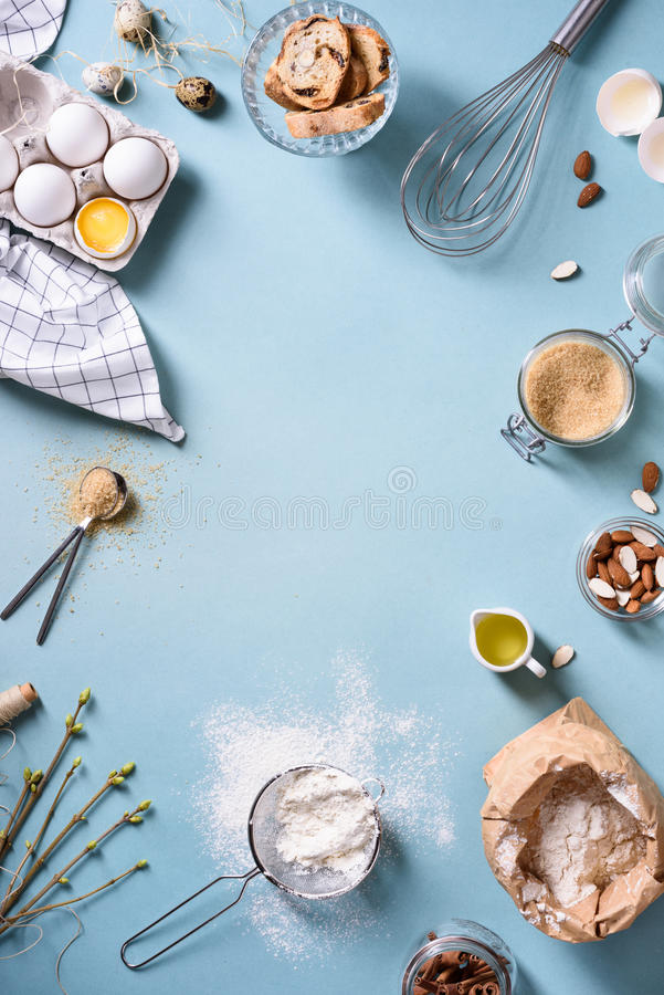Bakery background frame. Fresh cooking ingredients - egg, flour, sugar, butter, nuts over blue background. Spring cooking theme. Top view, copy space stock photos