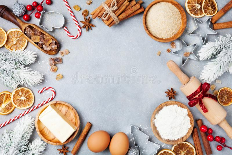 Bakery background with ingredients for cooking christmas baking decorated with fir tree. Flour, brown sugar, eggs and spices. stock photo