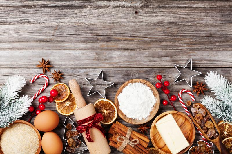 Bakery background with ingredients for cooking christmas baking decorated with fir tree. Flour, brown sugar, eggs and spices. royalty free stock image