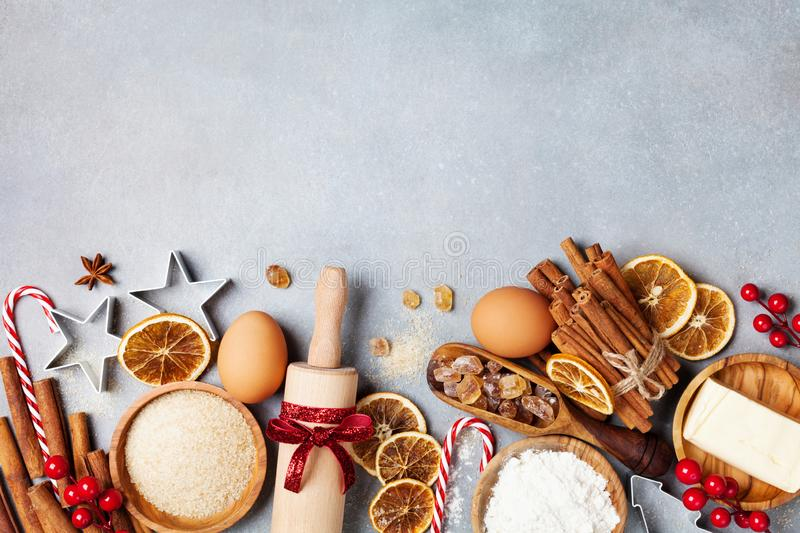 Bakery background with ingredients for cooking christmas baking decorated with fir tree. Flour, brown sugar, eggs and spices. royalty free stock photo