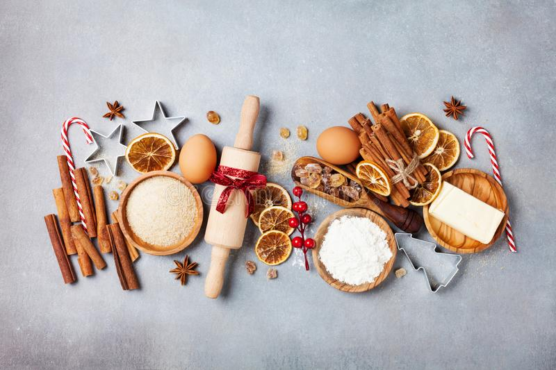Bakery background with ingredients for cooking christmas baking. Flour, brown sugar, eggs and spices on kitchen table top view. stock photo