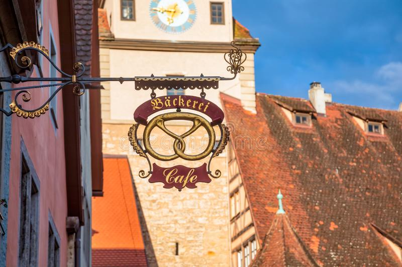 Bakery cafe sign with Old Town in background on Romantic Road Bavaria Germany. Backerei Bakery cafe sign with Pretzel representation with Old Town houses in stock photography