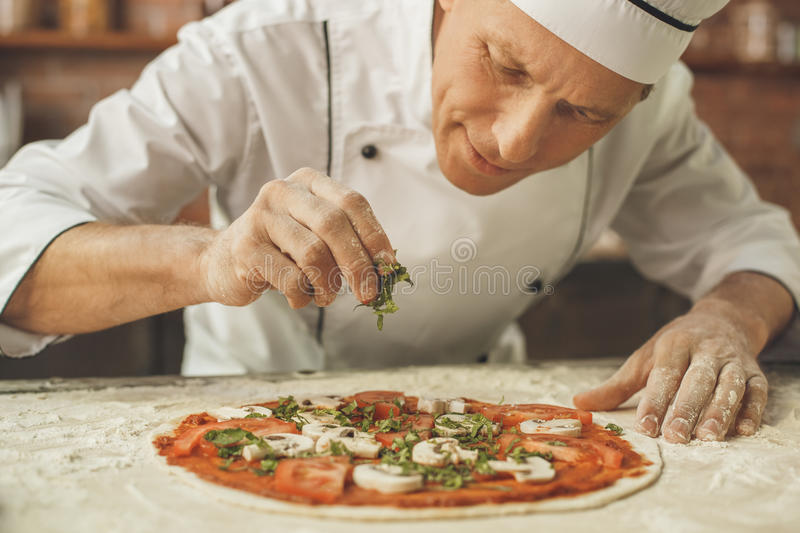 Bakery chef cooking bake in the kitchen professional. Making pizza stock photos