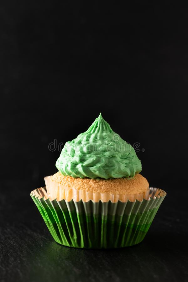 Bakery concept Homemade Sponge vanilla cupcake green tone buttercream on black background with copy space stock image