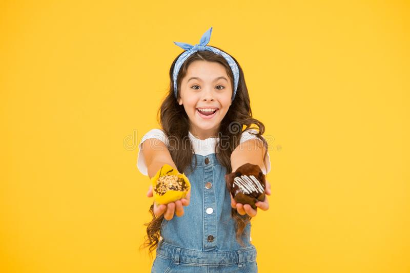 Bakery and confectionery concept. Kid girl hold glazed muffins. Delicious cupcakes. Happy childhood. Adorable smiling stock photography