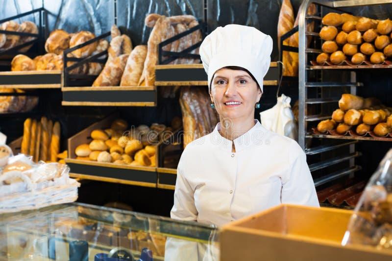 Bakery happy female employee with tasty bread stock image