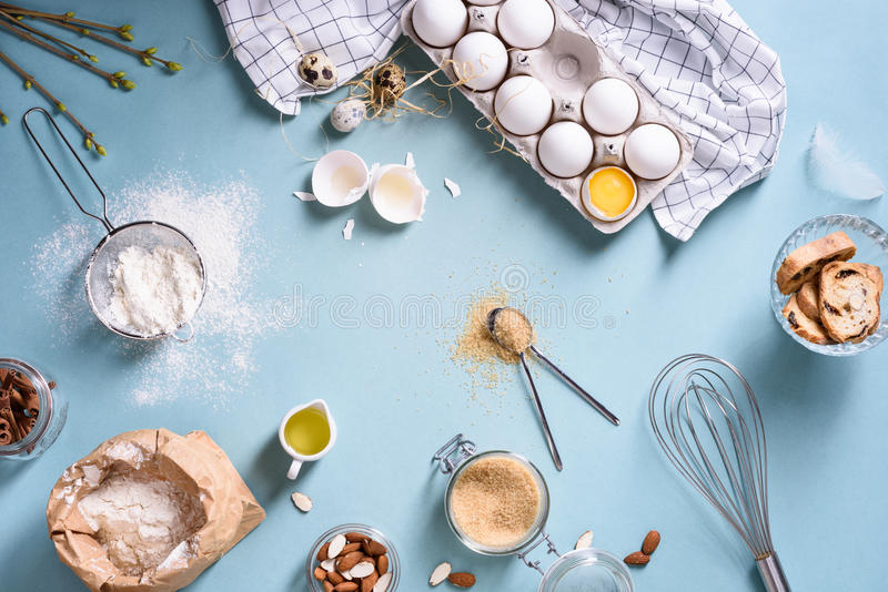 Bakery ingredients - flour, eggs, butter, sugar, yolk, almond nuts on blue table. Sweet pastry baking concept. Flat lay, copy royalty free stock photography