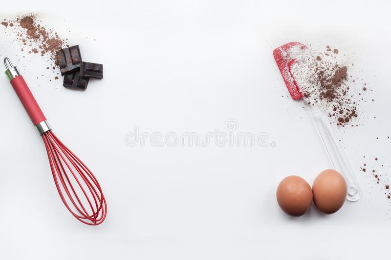 Bakery ingredients - flour, eggs, cocoa, chocolate on white table. Sweet pastry baking concept. Flat lay, copy space, top view stock images