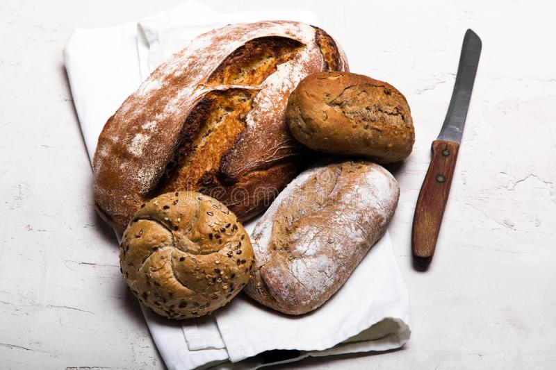 Bakery products, wholemeal bread and brown whole wheat buns. Tasty dark bread and buns  on white background, copy space. Bakery products, wholemeal bread and stock photo