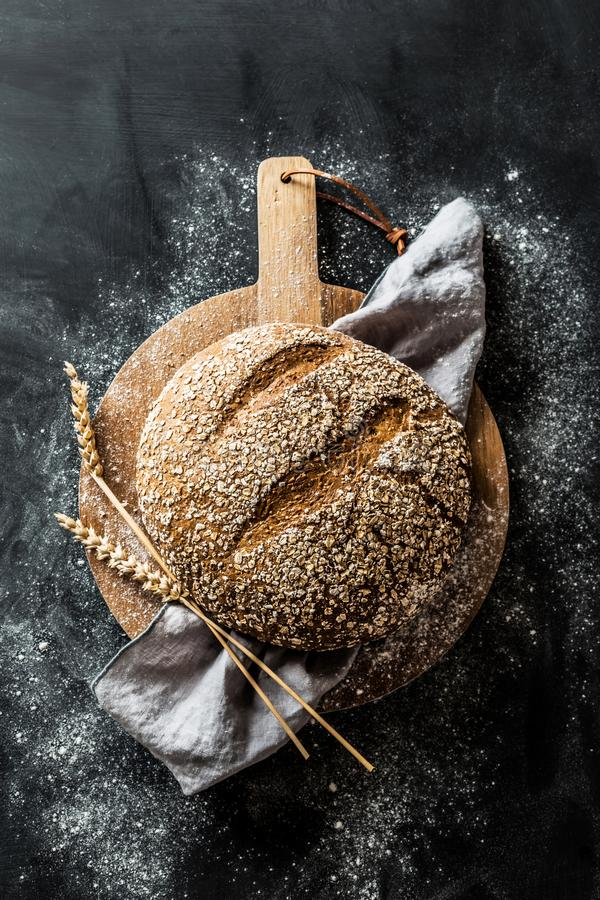 Bakery - round loaf of rustic bread on black background stock photos