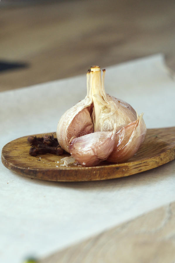 Bakes garlic bulb with spices on a wooden spoon royalty free stock image