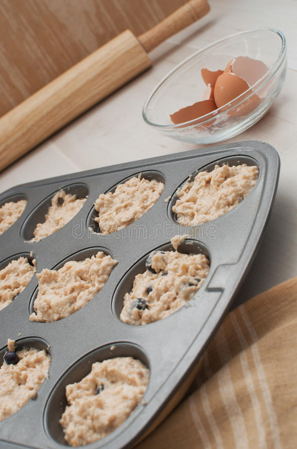 Bakeware with dough for muffins royalty free stock image