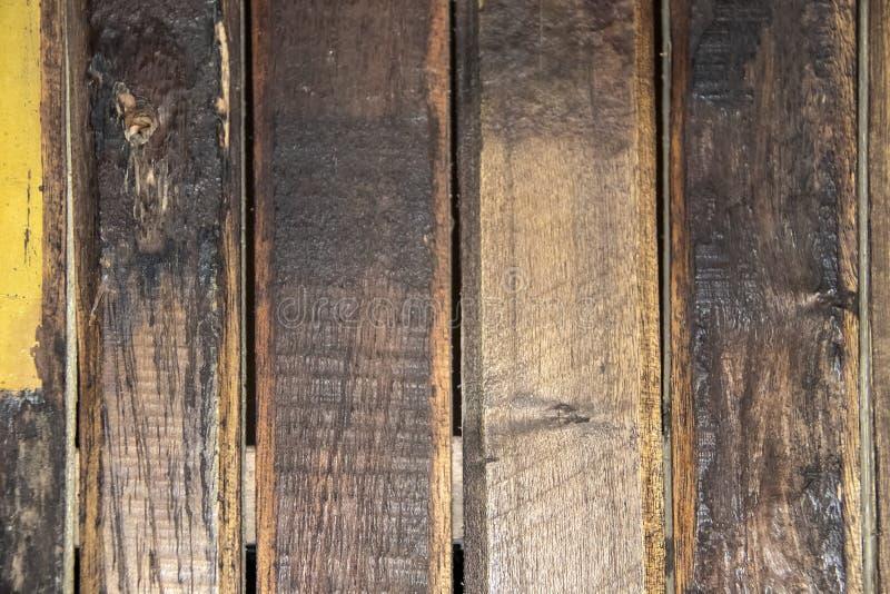 Bakgrund av bekymrade vertikala träplankor med på målat med en splotch av guling royaltyfria foton