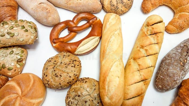 Bakgrund av blandade bakelser, bröd, kringlan, bagetten, gifflet, bullar stänger sig upp arkivfoton