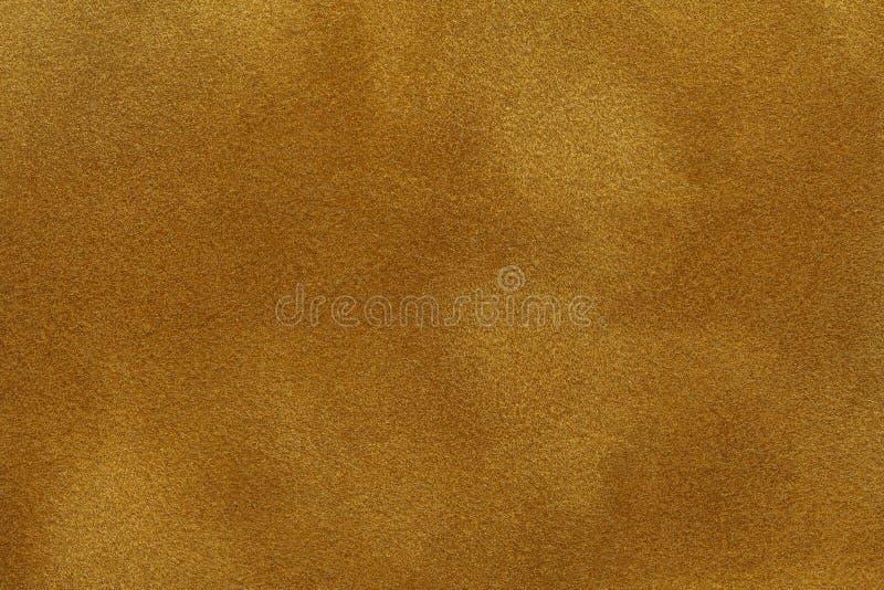 Bakgrund av den mörka guld- mockaskinntygcloseupen Matt textur för sammet av den gula nubucktextilen royaltyfri fotografi